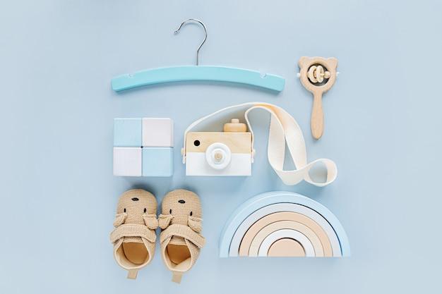 귀여운 신발, 이빨, 나무 장난감, 무지개. 밝은 파란색 배경에 소년을 위한 아기 물건과 액세서리 세트. 베이비 샤워 개념입니다. 패션 신생아입니다. 평평한 평지, 평면도