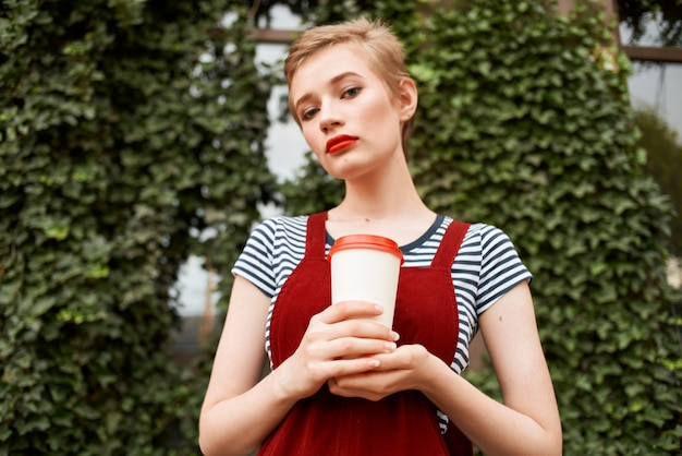 Cute short haired woman cup of coffee outdoors fun