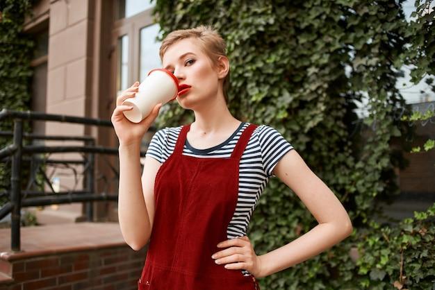 かわいい短い髪の女性のコーヒーの屋外の楽しみ
