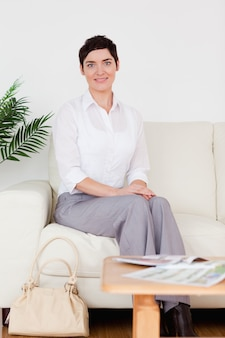 Cute short-haired woman sitting on a sofa