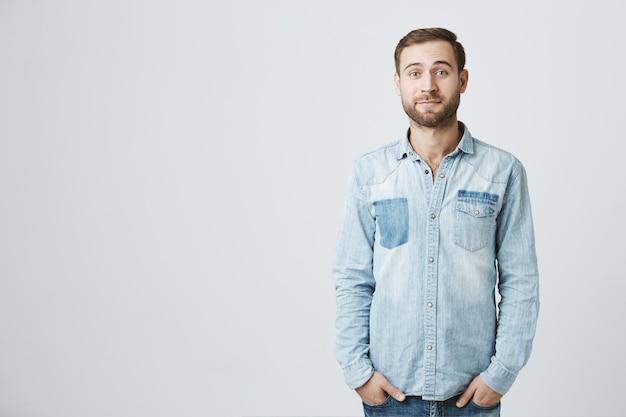 Cute shy bearded boyfriend in denim shirt, smiling