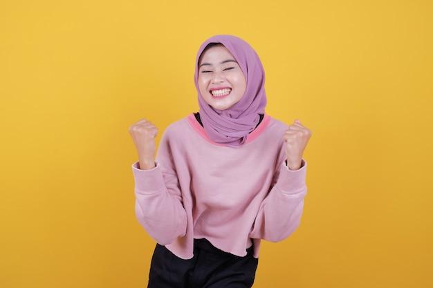 Симпатичная застенчивая девушка скромно улыбается и позирует с поднятыми руками