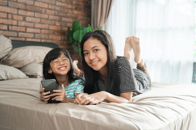 Cute sibling using mobile phone together