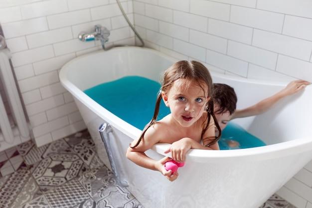 Cute siblings bathing in bathtub together in blue water