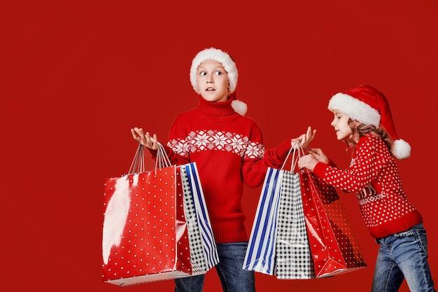 Симпатичные братья и сестры в красном свитере с сумками для покупок