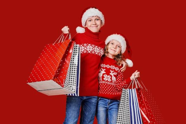 ショッピングバッグを保持している赤いセーターのかわいい兄弟