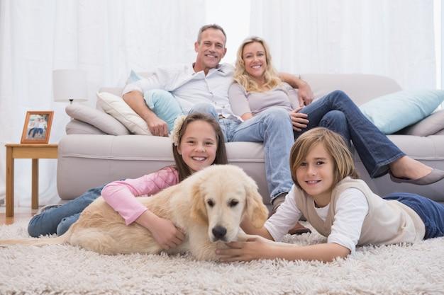 Симпатичные братья и сестры, играющие с собакой с родителями на диване