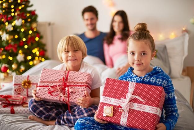 Cute siblings sitting in bed at christmas