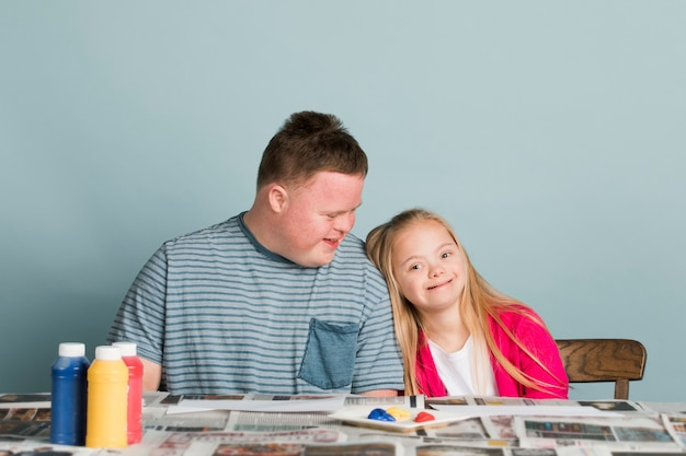Cute siblings with down syndrome playing with paint