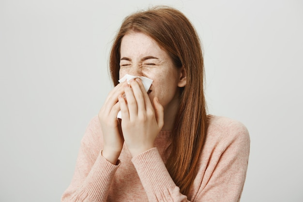 Cute sick redhead girl with allergy sneezing in napkin