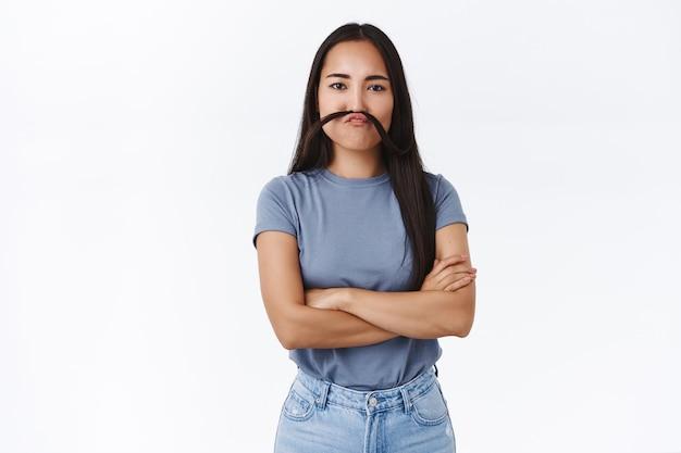 Симпатичная глупая азиатская девушка дурачится, имитирует смешные рожи, скрещивает руки на груди, как босс делает усы из прядей волос, и пристально смотрит в камеру, как будто она бизнесмен