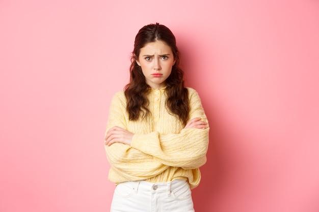 Симпатичная глупая девушка чувствует себя обиженной и грустной, пытается утешить себя объятиями, хмурится и смотрит в камеру оскорбленно, собирается плакать, стоя у розовой стены