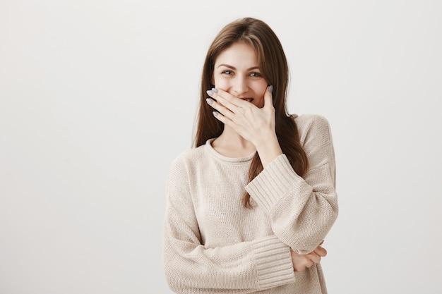 Симпатичная глупая девушка хихикает, улыбается рукой и смотрит в камеру весело