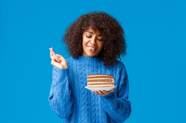 Carina e sciocca giovane donna afroamericana speranzosa in maglione, con taglio di capelli afro ricci, dita incrociate, buona fortuna, pregando e tenendo il piatto con una deliziosa torta grande, muro blu in piedi.