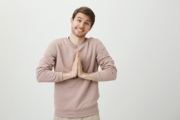 Милый глупый человек улыбается, умоляет, возьмитесь за руки в молитве, умоляя или скажите, пожалуйста