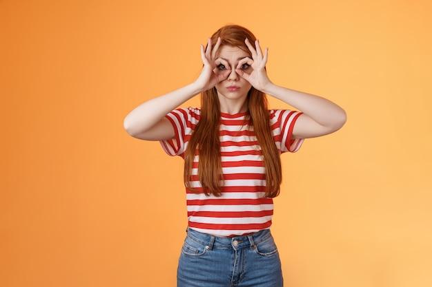 손가락 안경을 만드는 귀여운 바보 같은 빨간 머리 매력적인 소녀는 괜찮은 원 표지판을 통해 삐죽삐죽을 즐겁게 하고 있습니다...