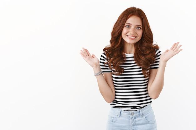 Carina ragazza rossa sciocca in maglietta a righe che alza le mani in segno di resa, scusandosi per un leggero inconveniente, errore, sorridente imbarazzata e timida, muro bianco
