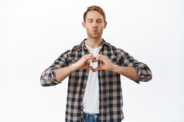 Uomo mascolino carino e sciocco rosso che mostra il segno del cuore, dì che ti amo, chiudi gli occhi e aspetta un bacio con le labbra che baciano arricciate, in piedi contro il muro bianco