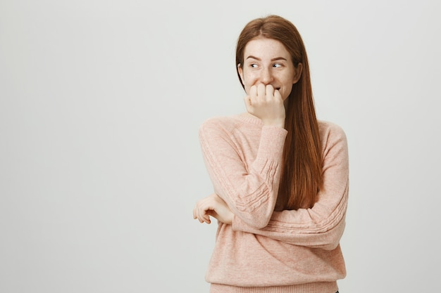 Симпатичная глупая рыжая девочка-подросток хихикает и смотрит налево на рекламу