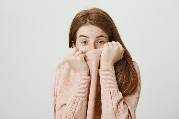 セーターの襟の後ろに顔を隠して恥ずかしそうに見えるかわいい愚かな赤毛の女性