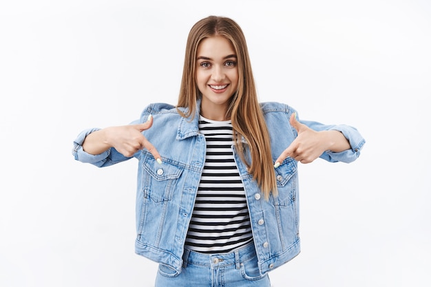데님을 입은 귀여운 금발의 행복한 십대 소녀, 손가락을 아래로 가리키고 카메라를 보고, 제안을 하고, 제품 프로모션을 소개하고, 최고의 할인을 제공하는 매장, 흰 벽 광고에 서 있는