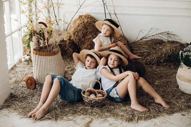 Cute sisters and brother in hay hats resting on hay