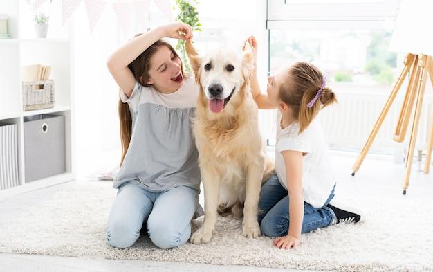 家の床に愛らしい犬の耳をいじるかわいい姉妹