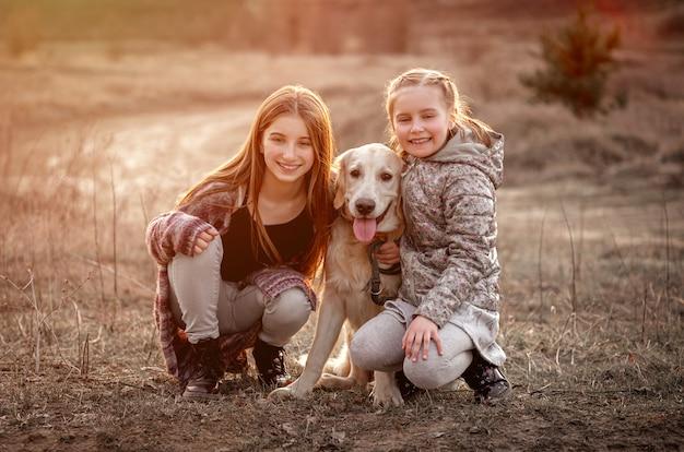 Cute sisters hugging dog outdoors