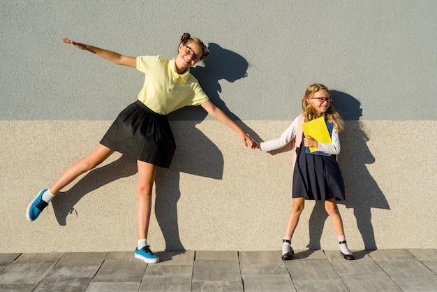 Cute sisters schoolgirls in school uniform.