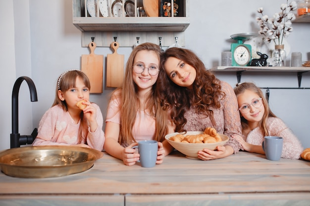 Cute sisters standing in a kitchen and eats buns