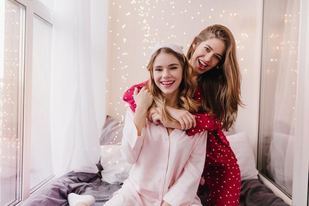 귀여운 자매들은 침실에서 장난 치는 트렌디 한 파자마를 입고 있습니다. 아침에 에너지를 표현하는 놀라운 백인 소녀.