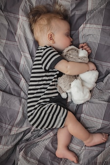 Cute six-month-old blond boy sleeping on a gray bed with a toy in his hands
