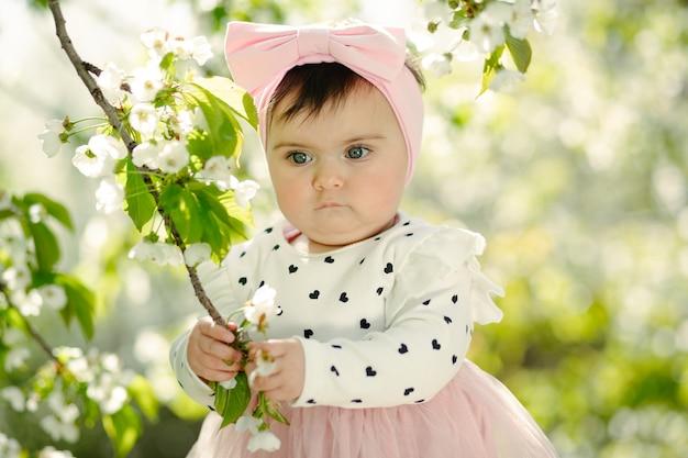 봄에 벚꽃 가지를 들고 귀여운 6 개월 된 아기