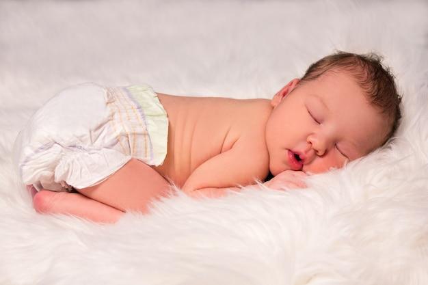 白い毛皮の毛布の上におむつでかわいい眠っている新生児