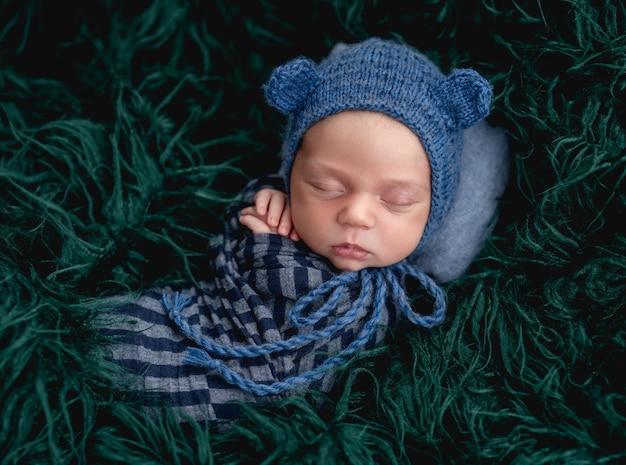 毛皮で青いニット帽をかぶってかわいい眠っている新生児