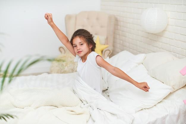 かわいい眠そうな女の赤ちゃん、ストレッチ、手を挙げて、朝寝た後