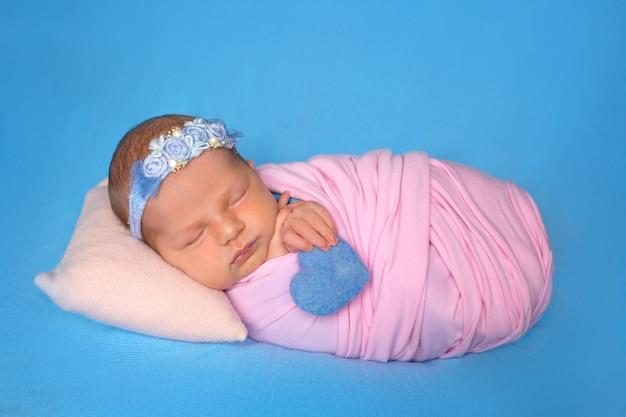 かわいい眠そうな生まれたばかりの赤ちゃんの女の子