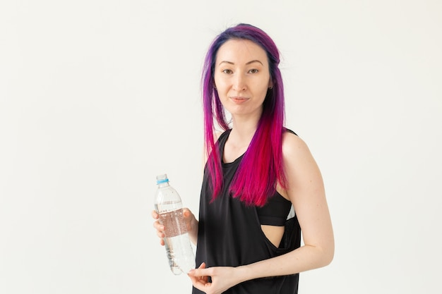 Cute slender young asian woman with colored hair drinking water after gym workout. concept of replenishing water balance and a healthy lifestyle. white background with copy space