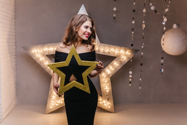 Cute slim brunette waiting for new year's party. girl in black dress posing with shiny star.