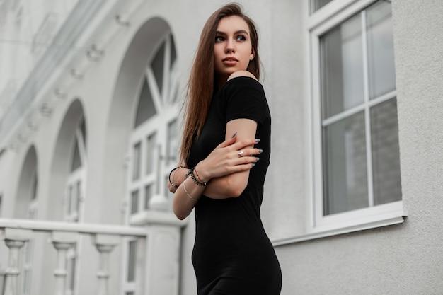 エレガントでセクシーな黒のドレスを着たかわいいスリムでファッショナブルな若い女性が、ヴィンテージの白い建物の近くの通りでポーズをとる。屋外で流行の服を着た美少女モデル。
