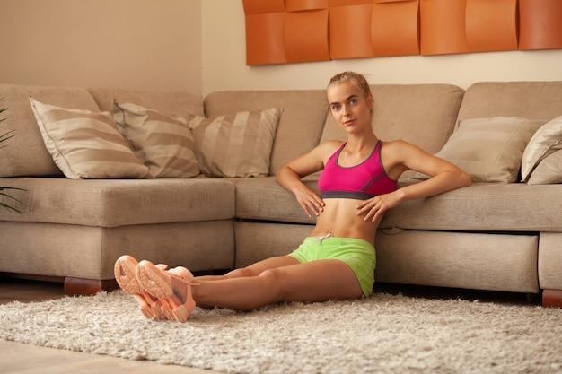 실내 운동을 할 준비가 된 집에서 소파 근처에 앉아 운동복을 입은 귀여운 슬림 피트니스 여성