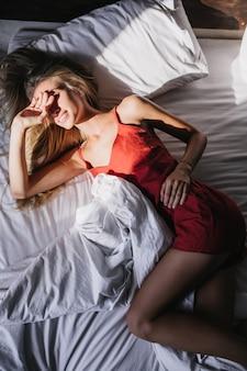 잠옷에 귀여운 슬림 여자가 침대에서 놀아요. 화창한 아침에 침실에 누워 영감을 된 금발의 여자.