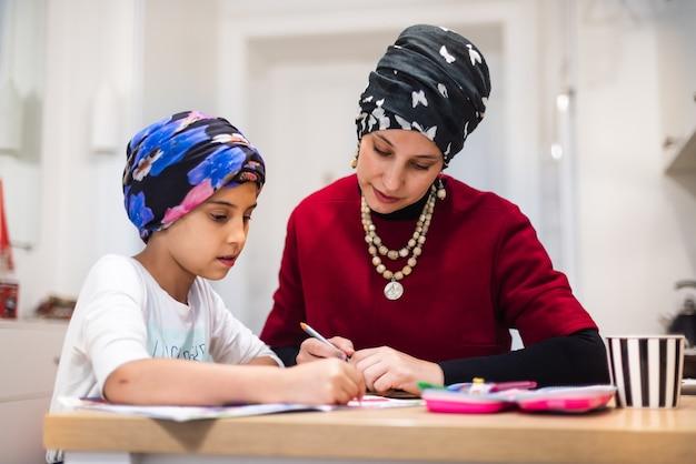 Милая маленькая дочь 6-7 лет учится письму с наставником молодой мамы