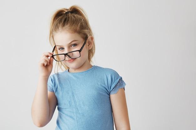 青い目と青いtシャツで楽しい笑顔のかわいい小さなブロンドの女の子が学校の写真用の新しいメガネで面白いポーズ。