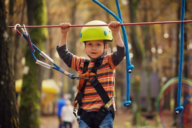 Cute small boy enjoying a sunny day in a climbing adventure acti