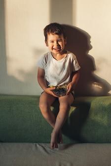 かわいい小さな男の子は、自宅のソファに座ってブルーベリーを食べながらカメラに微笑んでいます