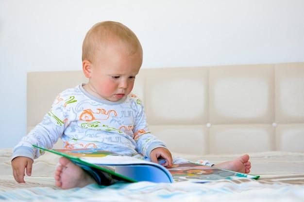 Милый маленький мальчик сидит на плохом и читает книгу