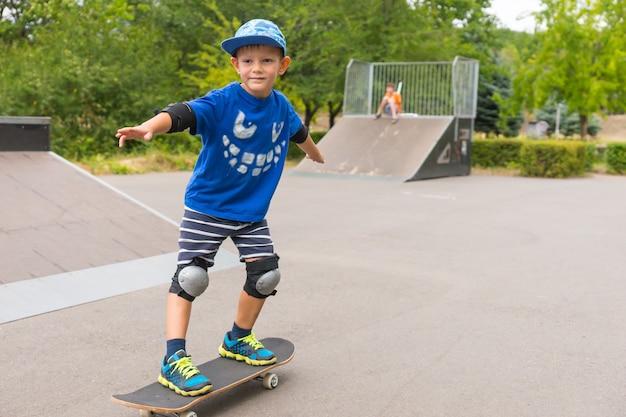 幸せな笑顔でボード上で彼のスタンスを練習しているスケートパークでスケートボードをしているかわいい男の子