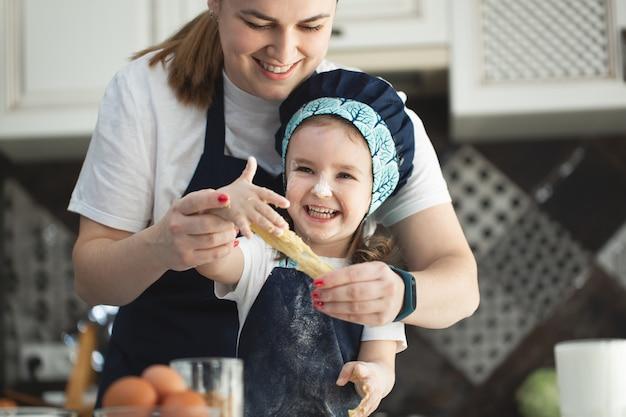 현대 부엌에서 함께 그릇에 반죽을 준비하는 엄마 반죽을 돕는 귀여운 작은 아이 딸.