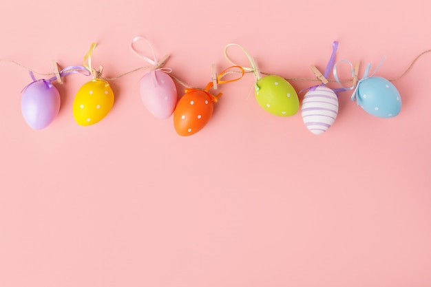 Cute small colorful eggs on pink